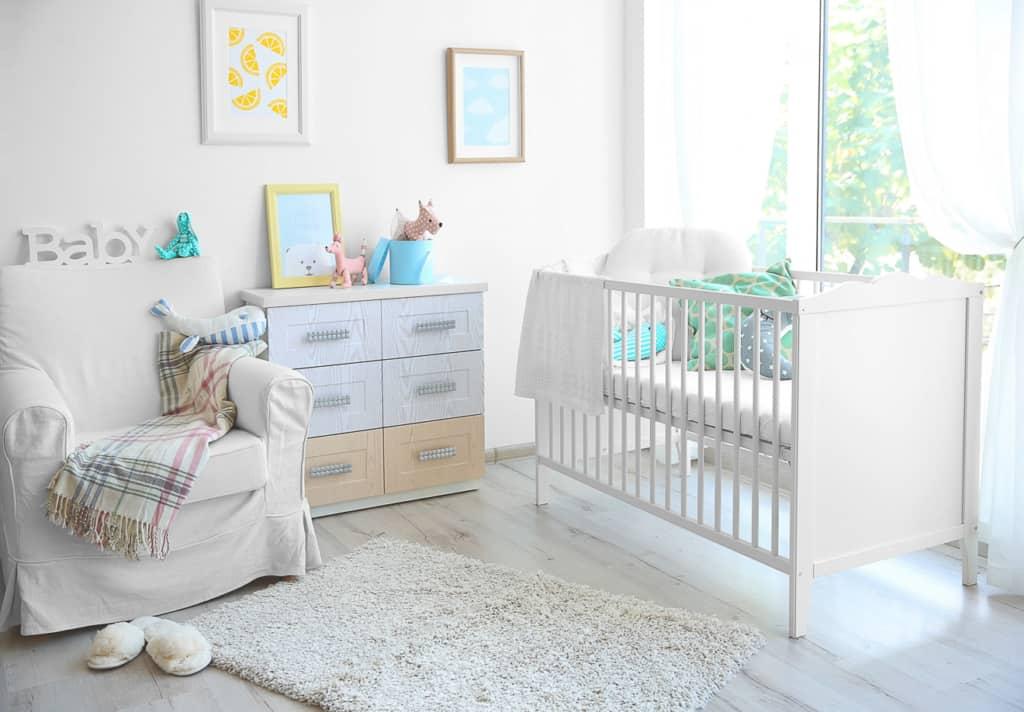 Inneneinrichtung des modernen Babyzimmers - Babybett mit Kommode