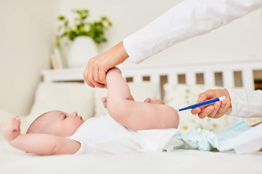 Mutter misst mit einem Fieberthermometer die Temperatur von Baby