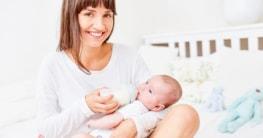 Glückliche Mutter gibt ihrem Baby die Flasche