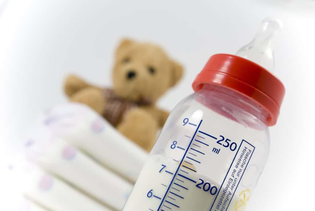 Ein Stapel Windeln, Babyflasche und ein Teddybär vor weißem Hintergrund