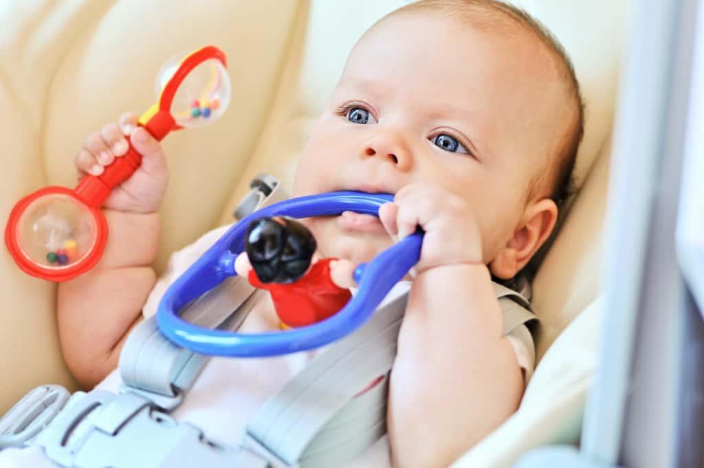 Baby in einer Babywippe mit Babyspielzeug