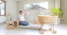 Schwangere Frau bei Einzug mit Babysachen und Stubenwagen
