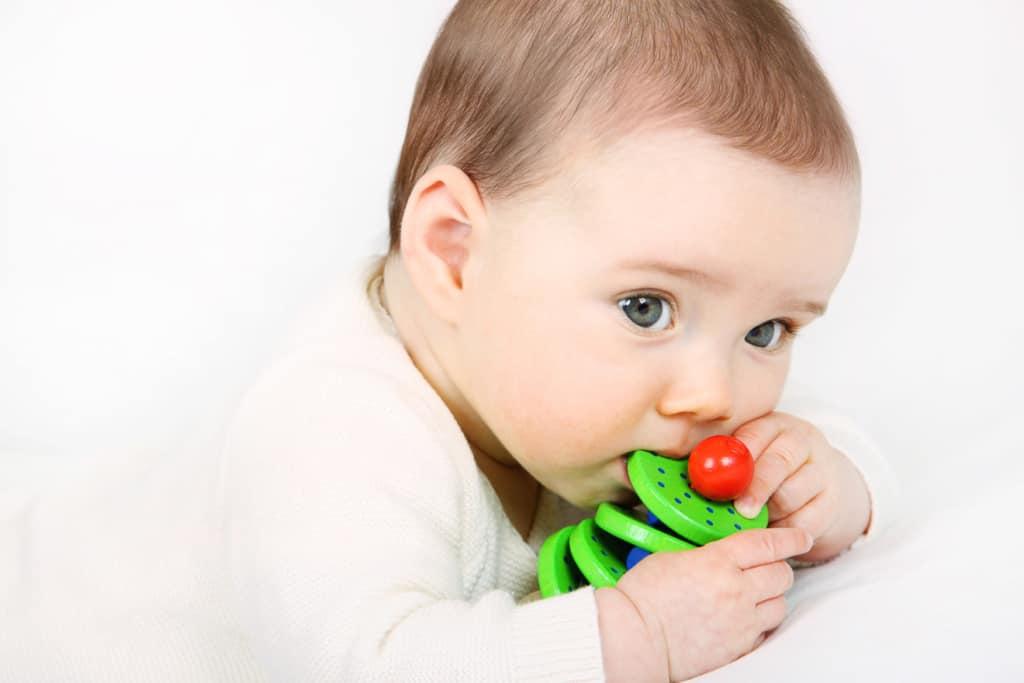 Ein Baby spielt mit einem Greifling aus Holz