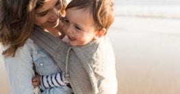 Mutter mit Babybauchtrag am Strand